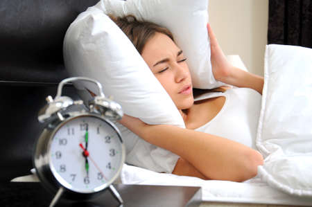 snooze: Young woman getting stressed about waking up too early