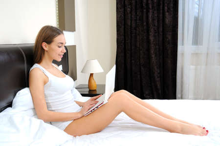 Young beautiful happy woman lying on the bed with laptop photo