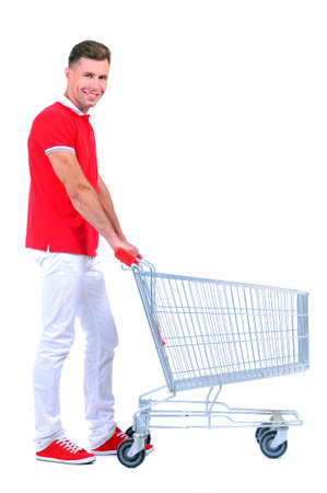 empty shopping cart: Full length portrait of a man posing next to an empty shopping cart isolated on white background Stock Photo