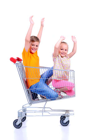 two children - girl and baby - with shopping cart in supermarket photo