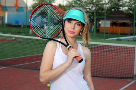 Pretty sportswoman with racket at the tennis court  Healthy lifestyle photo