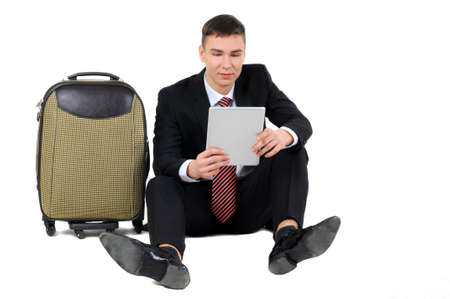 A businessman with tablet traveler waiting seated next to suitcase isolated on white background photo