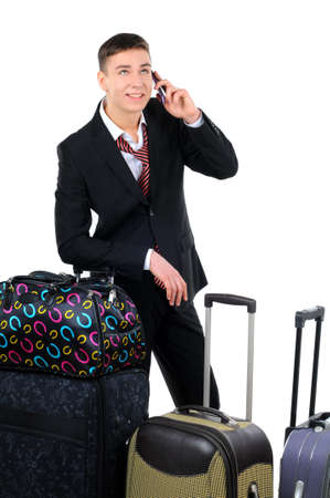 business traveler: Business traveler carrying a suitcase and talking on a cell phone isolated on white background Stock Photo