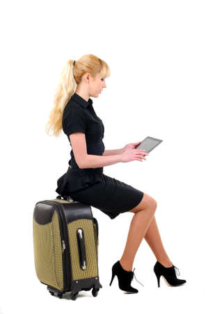 A tourist girl with tablet seated on to a suitcase isolated on white background photo