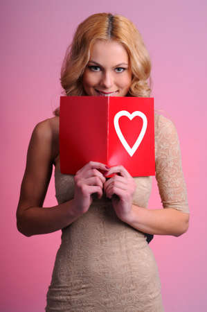 Girl with a greeting card on a pink background  Valentines day photo