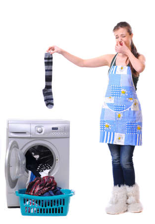 A housewife holding a male sock and her nose next to a washing machine isolated on white photo