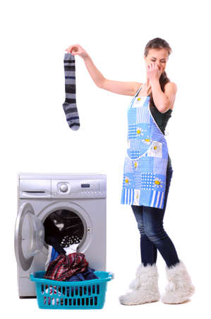 household tasks: A housewife holding a male sock and her nose next to a washing machine isolated on white