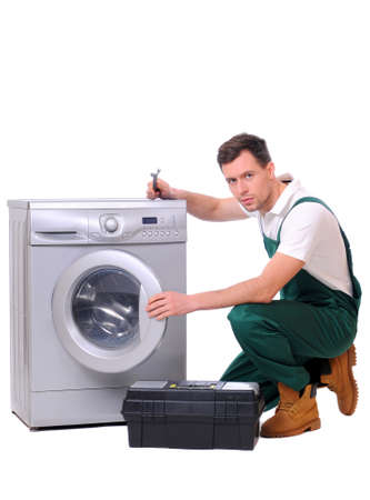 A repairman holding a spanner and posing next to a washing machine isolated on white background photo