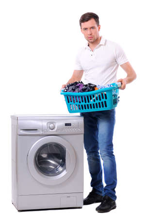 man with laundry basket posing next to a washing machine isolated on white background photo
