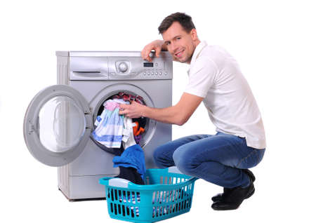 household tasks: young male next to a washing machine isolated against white background