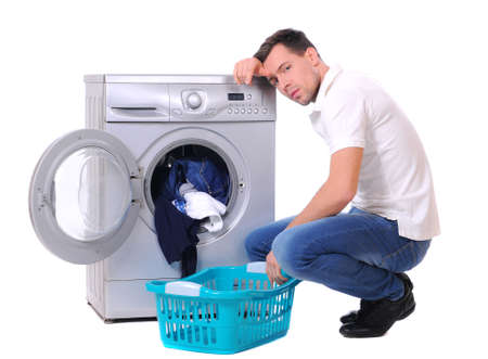 dilema: young male next to a washing machine isolated against white background