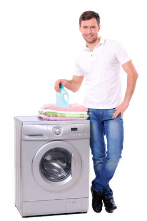 young male next to a washing machine isolated against white background photo
