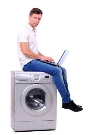 lavadora con ropa: hombre joven con ordenador port�til sentado en la lavadora