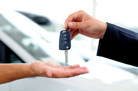 buying a car: Handover of car keys in a dealership