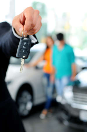 Handsome young classic car salesman standing at the dealership holding a key for a car photo