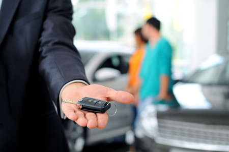 new contract: Handsome young classic car salesman standing at the dealership holding a key for a car Stock Photo