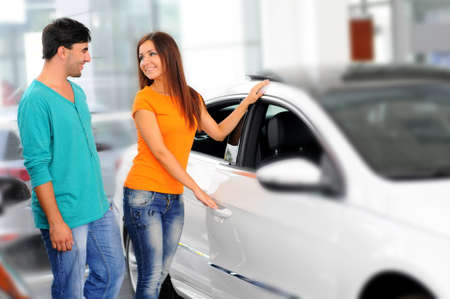Happy couple chooses to buy a car in showrooms photo