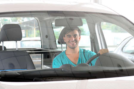 stetting: Young man looking car that wants to buy in the showroom