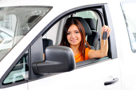 stetting: Join me for a drive. Attractive young woman sitting at the front seat of the car looking at camera Stock Photo