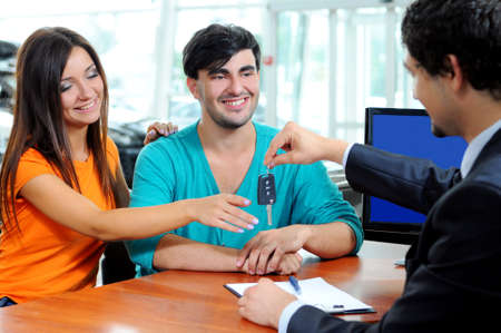 outstretching: Car Dealer signing a contract to purchase and giving the key to a new car to a young attractive owners Stock Photo