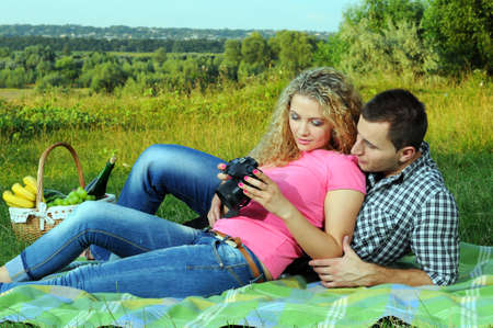 Loving young couple photographed and is looking at the photographs they made on a picnic photo