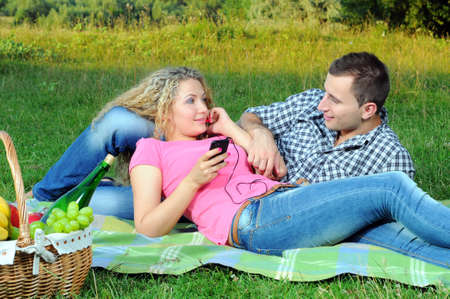 Loving young couple listening to the music in headphones on picnic together photo