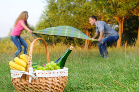 Happy couple with a romantic picnic blanket lay on the background of a basket of fruit and wine photo