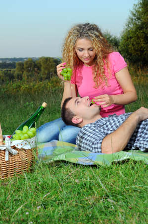 Young couple feeding each other with a grapes bunch on the picnic photo