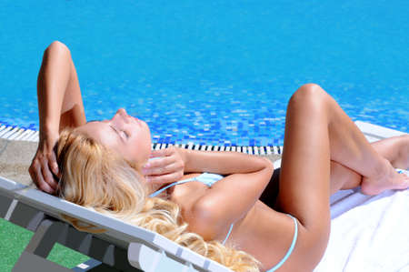 Relaxing on the deck chair. Beautiful young women relaxing on the deck chair near the pool photo