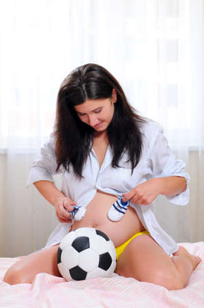 desirable: young pregnant woman with a soccer ball and athletic shoes for baby. waiting for the boy