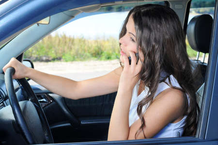 view through door: An attractive young Caucasian woman talking on the phone from the front seat of the car