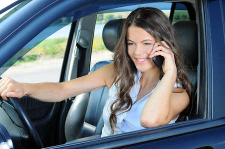 An attractive young Caucasian woman talking on the phone from the front seat of the car photo