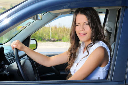An attractive young Caucasian woman winking at the camera from the front seat of the car