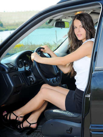 drive through: An attractive young Caucasian woman looking at the camera from the front seat of the car Stock Photo