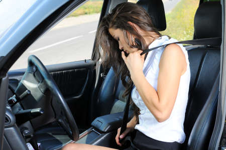 An attractive young Caucasian woman fastening her seat belt before the car trip on the front seat of the car photo