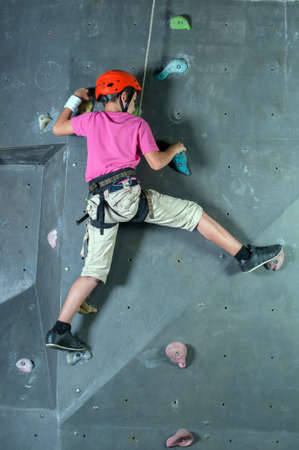 Child climbing on a wall in a climbing center. photo