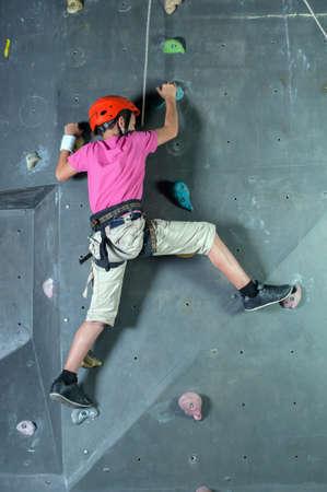ni�o escalando: Ni�o que sube en una pared en un centro de escalada. Foto de archivo