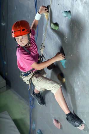niño escalando: Niño que sube en una pared en un centro de escalada. Foto de archivo