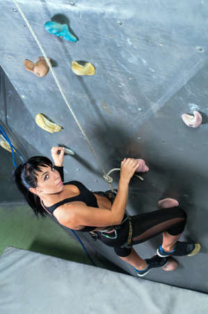 Women climbing on a wall in an climbing center photo