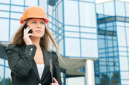 Female civil engineer talking on the phone building in the background photo