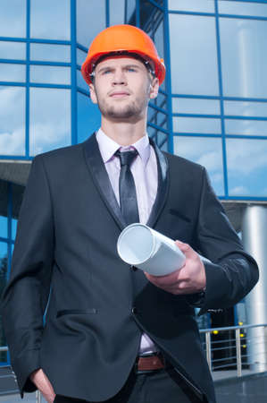 Engineer in front of modern building with plan photo