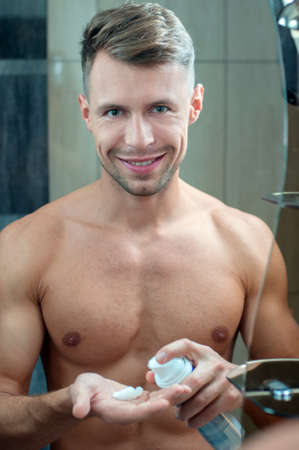 bare chested: Reflection of a young man shaving in bathroom mirror