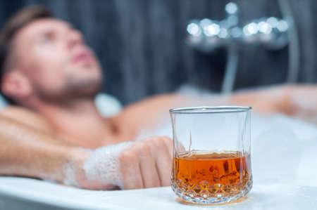 jeune homme de prendre un bain, boire du whisky