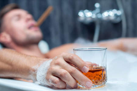 young man taking a bath, drinking whiskey and smoking cigar photo
