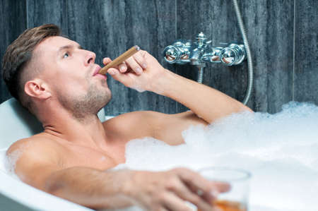 young man taking a bath, drinking whiskey and smoking cigar photo