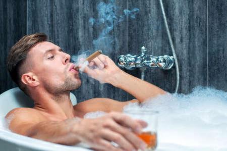 hombre fumando puro: joven de tomar un baño, beber whisky y fumar cigarros Foto de archivo