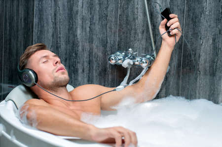 young man taking a bath, listening to music from the player photo