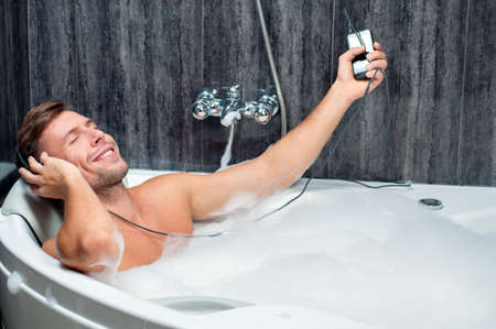 bathtubs: young man taking a bath, listening to music from the player