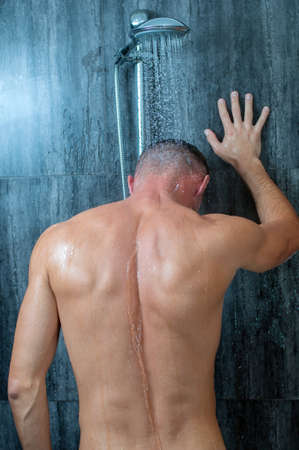 taking shower: Close-up of a young man taking a shower Stock Photo