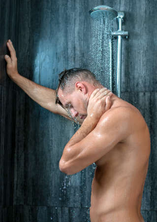 Close-up of a young man taking a shower photo